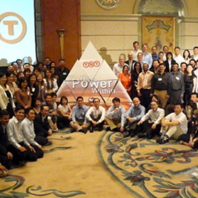 Group of people sitting and standing around a gigantic cardboard pyramid that they built together during Orangeworks team building event.