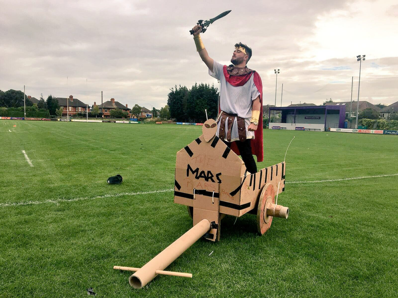 A delegate of Orangeworks fun team building games Flat Out Chariots standing in his cardboard chariot.