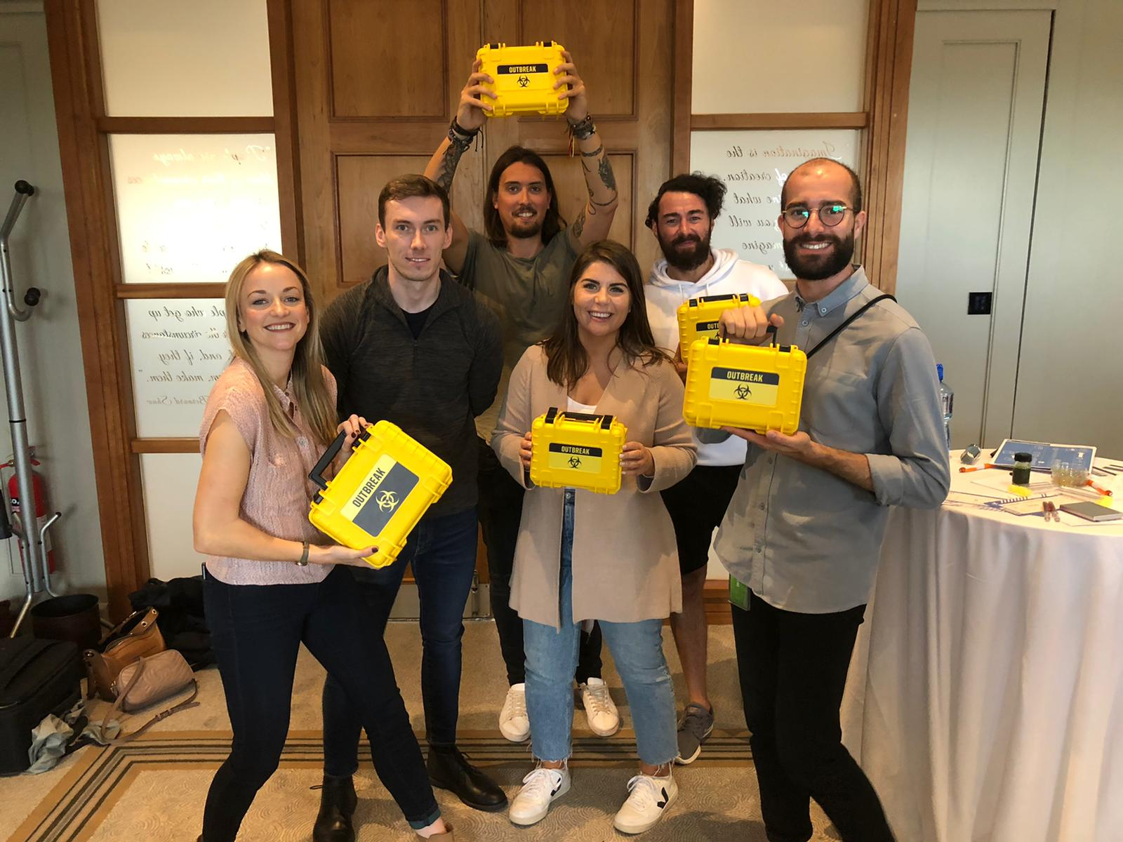 Delegates holding their Outbreak boxes as they have just finished their team building activities with Orangeworks.