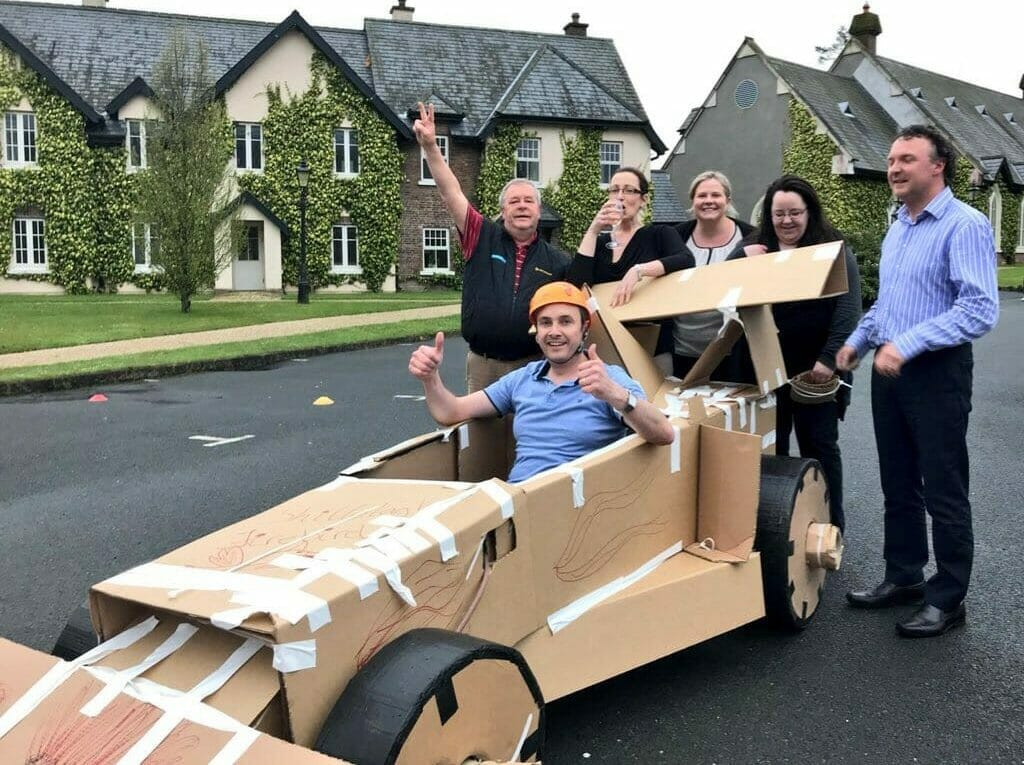 Delegates preparing to race the formula one car they made during their staff day out with orangeworks.