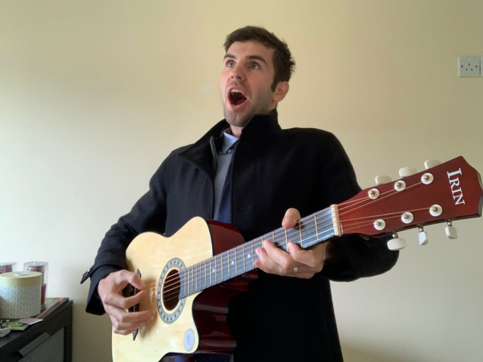 A delegate pretending to play his guitar while playing Orangeworks remote team building activity Picture Perfect.