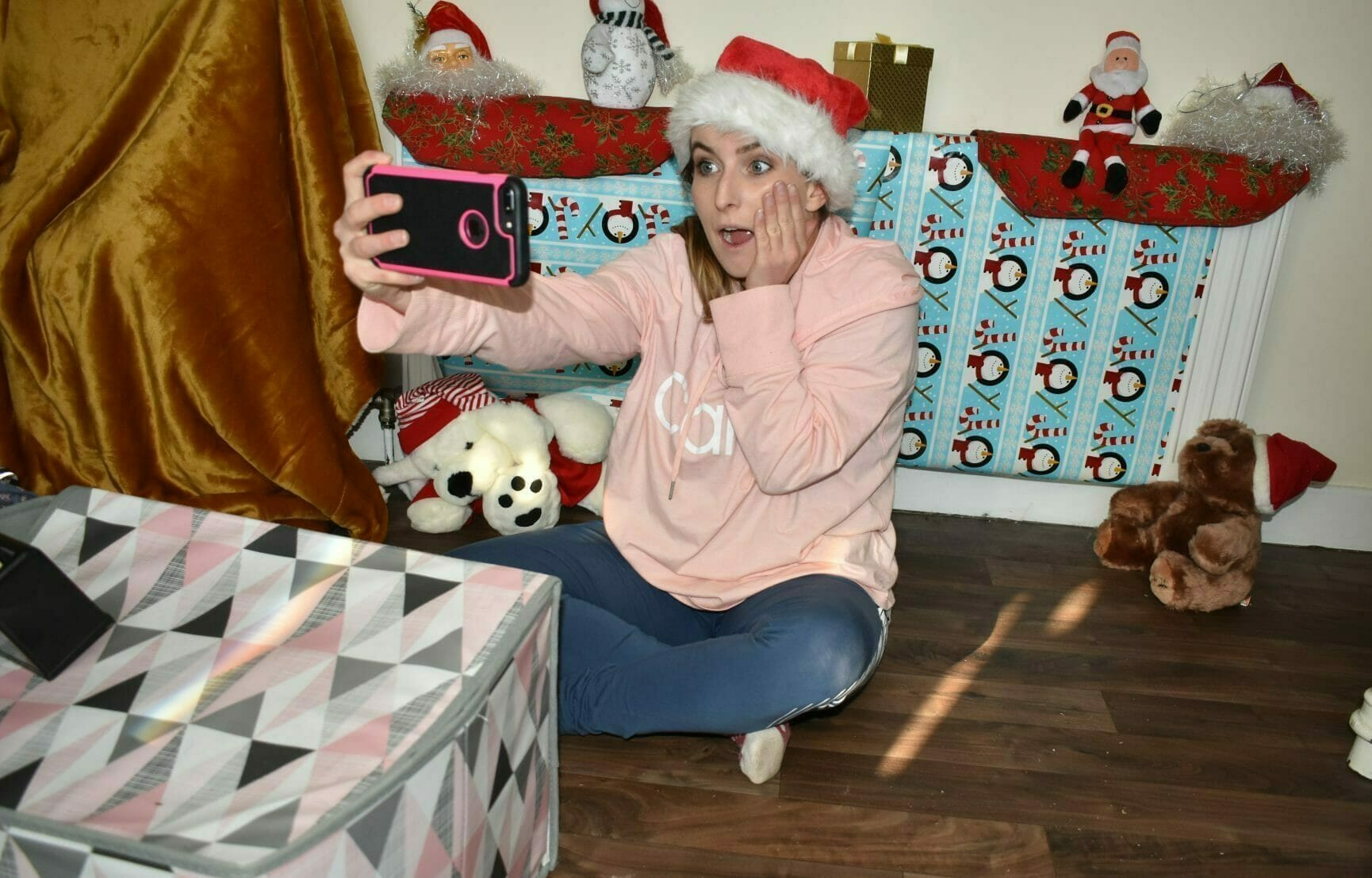 A delegate taking photos with her Christmas decorations playing Blockbusters on Location, a virtual game for team building.