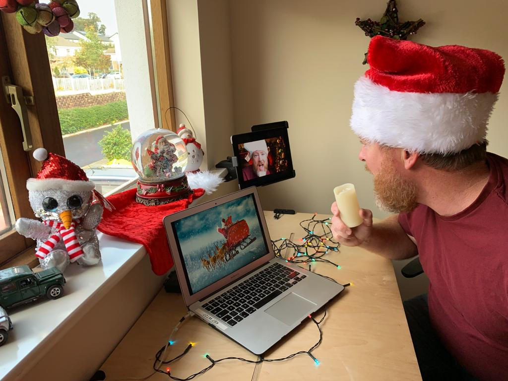 Delegate sitting in front of his laptop with his Christmas setup, playing one of Orangeworks virtual Christmas office games.
