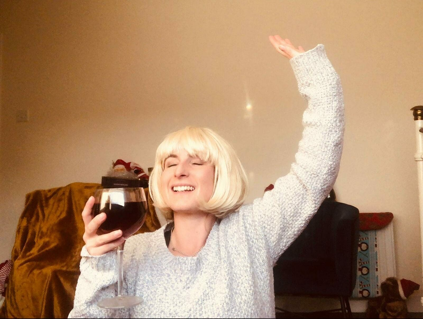 Delegate wearing a blonde wig recreating a famous Christmas photo for one of Orangeworks virtual Christmas games for work.
